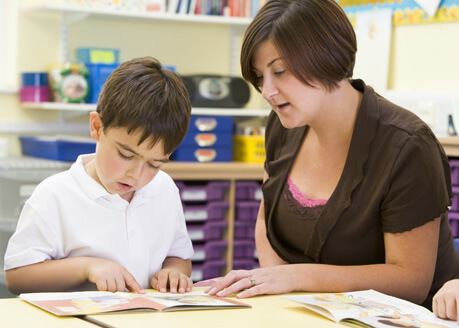 Photo of child reading to adult to demonstrate the role of the designated teacher